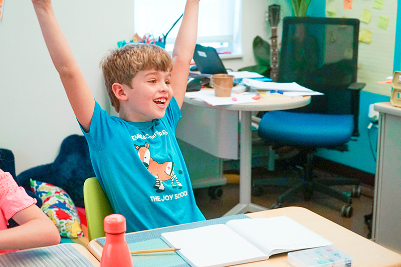 Student cheering for his victory in Adventure Math with his arms raised