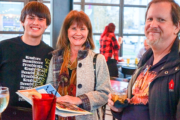 a young man, mother, and teacher smiling in a restaurant