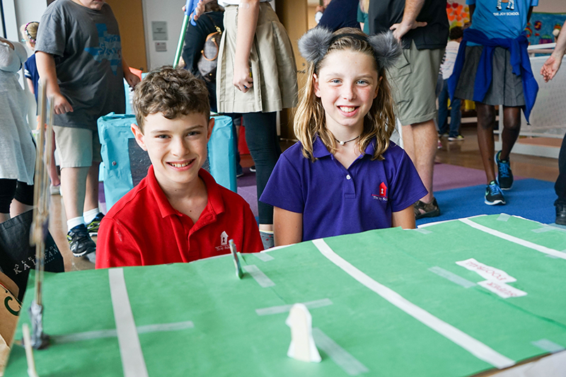Two students pose next to the cardboard and construction paper football field they created