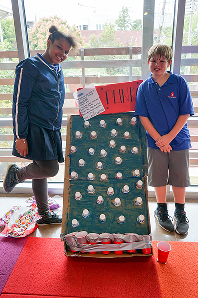 Two students pose next to their cardboard game, stuffed with paper cups, called Plinko