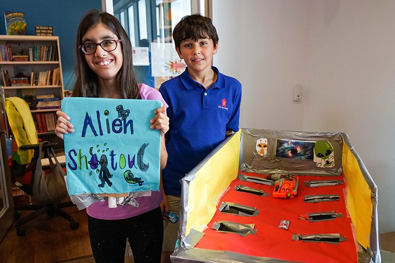 Students pose next to their game, alien shootout