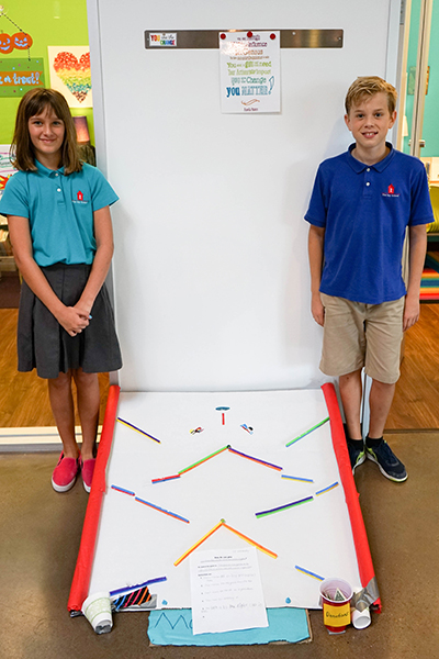 students pose next to their cardboard ramp game