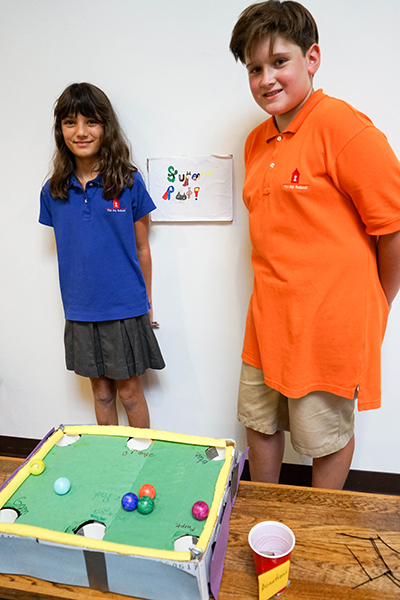 students pose with their cardboard pool table