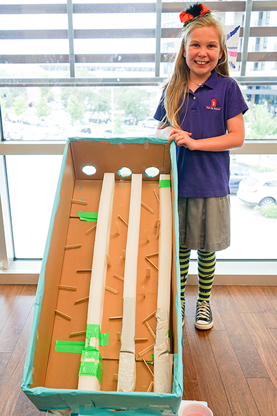 student poses next to her game made of cardboard and Popsicle sticks