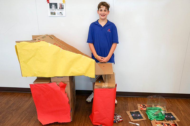 a student poses next to his intricate cardboard ramp and water pool