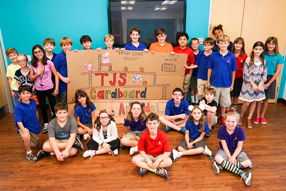 All participants in the cardboard arcade pose next to a sign