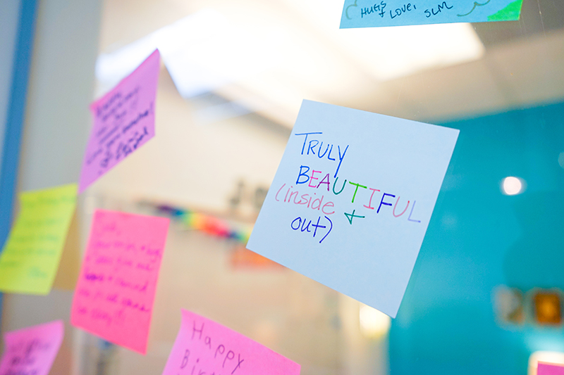 "Sticky notes on a door. The closest one is white with rainbow lettering that  reads ""Truly Beautiful (inside & out)"