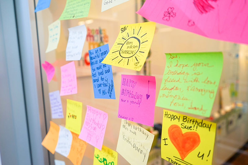 Lots of colorful sticky notes with kind words written on them, attached to a clear glass door.