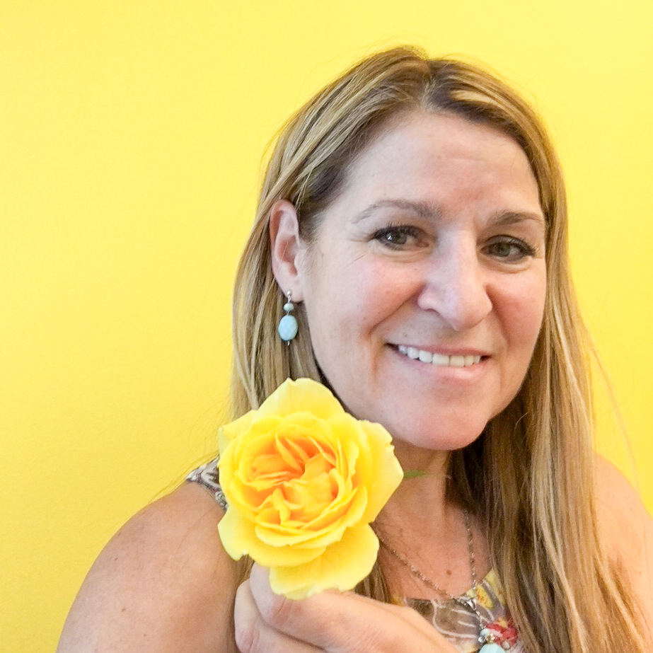 Mrs. Wilson holding a yellow rose in front of a yellow wall.