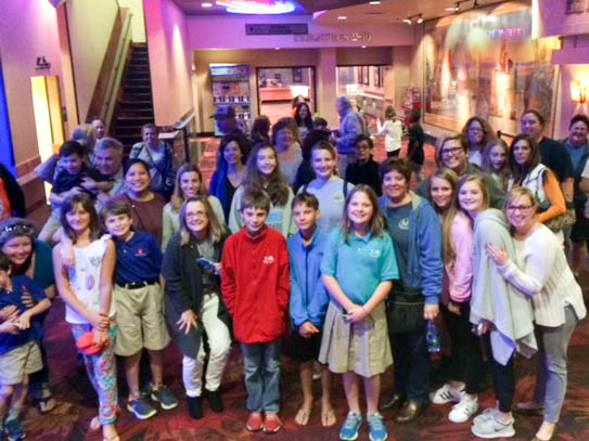 TJS students, alumni, teachers and families posing in the movie theater lobby